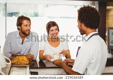 Barista serving two happy customers at the coffee shop - stock photo