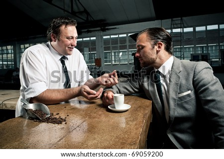 Barista shows customer the coffee bean he is drinking - stock photo