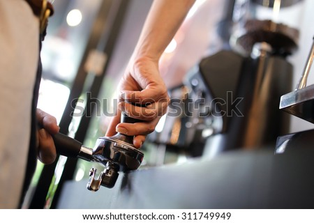 Barista using a tamper.  - stock photo