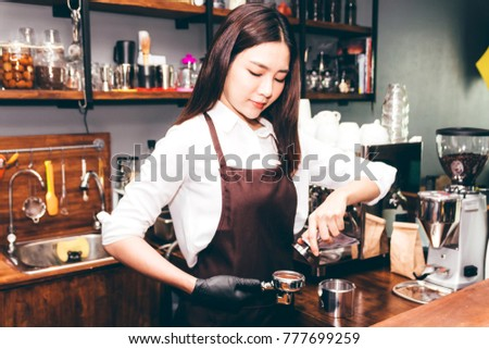 Barista using tamper to makes coffees in coffee bar