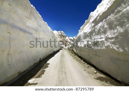 Barlachala pass in Leh Manali Highway, roads through ice walls with snow peak of himalaya in background - stock photo