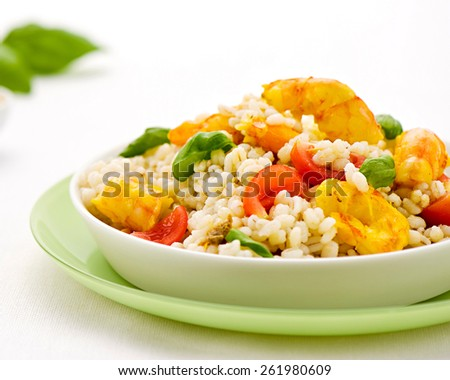 Barley and seafood salad with spicy yellow prawns, tomato and diced green vegetables served as a tasty appetizer to a dinner - stock photo