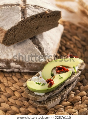 Barley bread slice with fresh avocado, cheese spread and tomatoes on a rustic background - stock photo