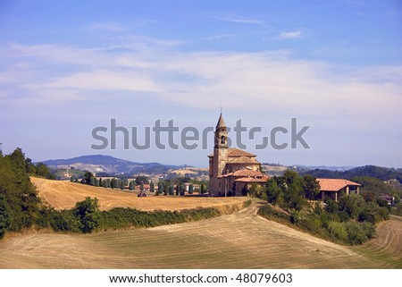 Barley field and church of Montesegale, Italy. - stock photo