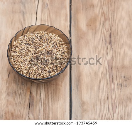 Barley grains of malt in glass bowl - stock photo