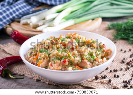Barley porridge in a bowl with meat and  vegetables