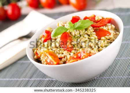 Barley with pesto sauce and tomatoes.