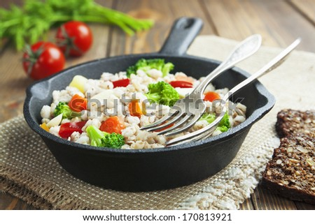 Barley with vegetables in the frying pan on the table