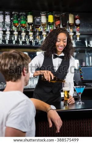 Barmaid pouring beer into beer glass for serving a man at bar counter in bar - stock photo