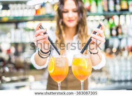Barmaid preparing cocktails in a bar for her clients - Bartender at work in a club - stock photo