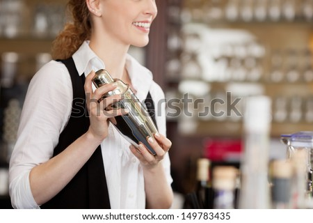 Barmaid shaking a cocktail shaker as she stands behind the bar mixing a drink for a client - stock photo