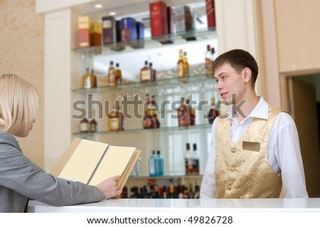 barman and blonde woman with wine list at restaurant bar - stock photo