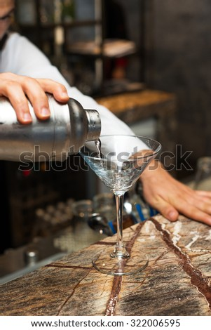 Barman at work, preparing cocktails. pouring cocktail to glass. concept about service and beverages. - stock photo