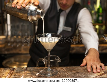 Barman at work, preparing cocktails. pouring pina colada to cocktail glass. concept about service and beverages. - stock photo
