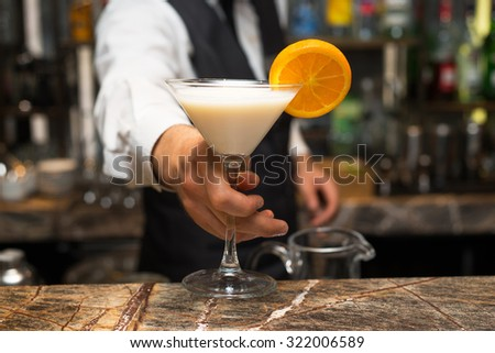 Barman at work, preparing cocktails. Serving pina colada. concept about service and beverages. - stock photo