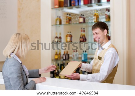 barman gives wine list to blonde woman at restaurant bar - stock photo