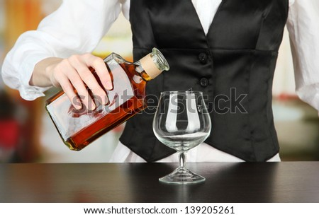 Barman hand with bottle of cognac  pouring drink into glass, on bright background