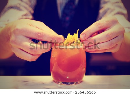 Barman is decorating cocktail with lemon zest, toned image - stock photo