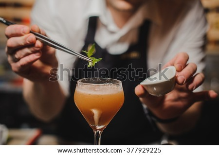 Barman is decorating cocktail with rocket no face - stock photo