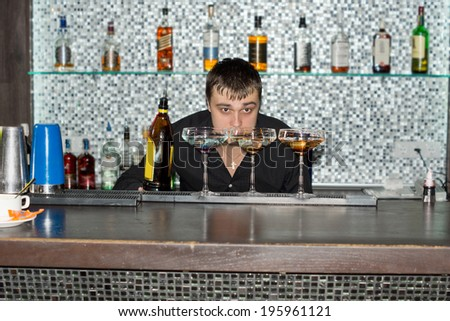 Barman keeping an eye on the cocktails he is mixing bending down low to check the liquid after adding a liqueur from a bottle - stock photo