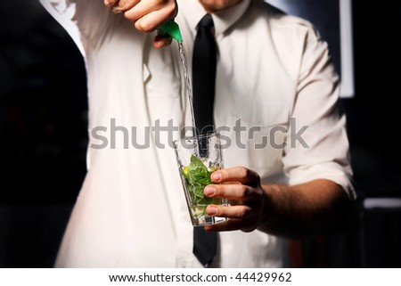barman making drink with mint and ice