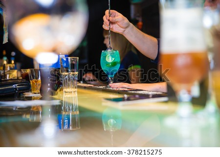 Barman pouring a cocktail - stock photo