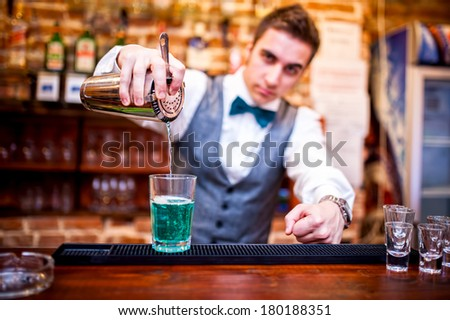 barman pouring a cocktail drink and looking at camera - stock photo