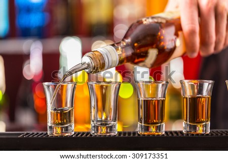 Barman pouring hard spirit into glasses in detail - stock photo