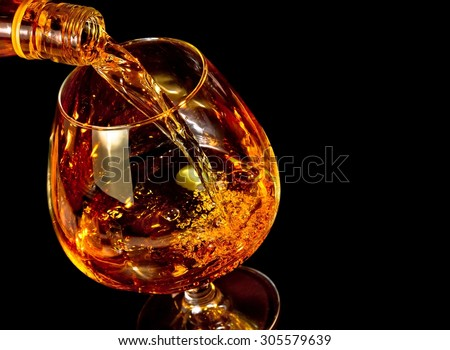 barman pouring snifter of brandy in elegant typical cognac glass on black background with space for text - stock photo