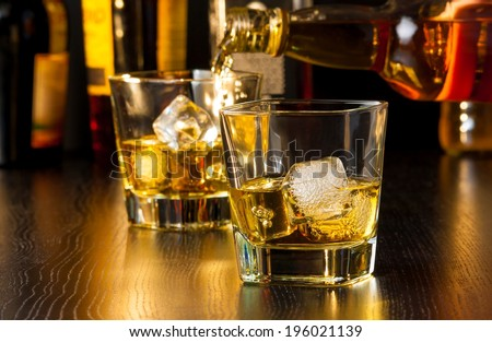 barman pouring whiskey behind whiskey glass on wood table - stock photo