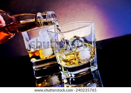 barman pouring whiskey in front of whiskey glass on light tint blue disco on black table with reflection - stock photo