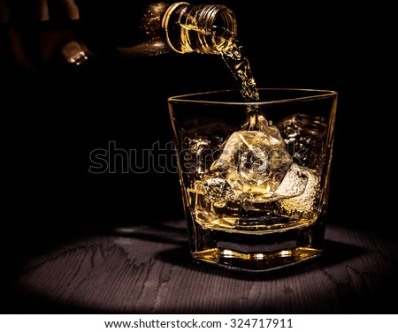 barman pouring whiskey in the glass on wood table, warm atmosphere, old style, time of relax with whisky with space for text - stock photo