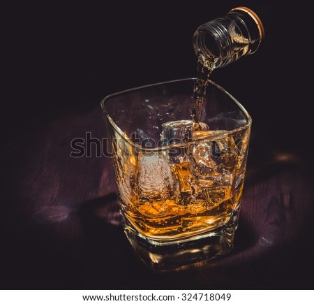 barman pouring whiskey in the glass on wood table, warm atmosphere, old western style, time of relax with whisky  - stock photo