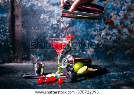 barman preparing and pouring red cocktail in martini class. cosmopolitan cocktail on metal background - stock photo