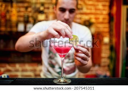 barman preparing cosmopolitan alcoholic cocktail drink at bar. Alcoholic drink with vodka, triple sec, cranberry juice and lemon juice - stock photo