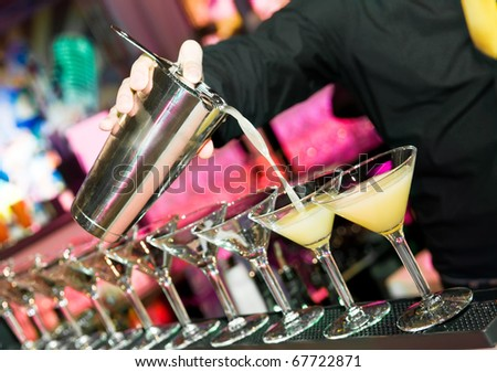 barman?s hand with shake mixer pouring cocktail into glasses arranged in a line - stock photo
