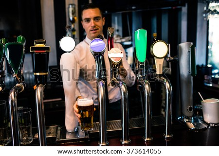 Barman serving a pint of beer in a bar - stock photo