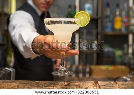 Barman serving margarita cocktail - stock photo