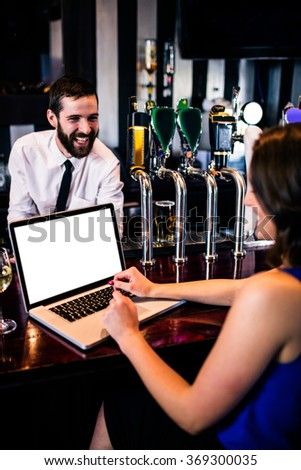 Barman talking to customer using laptop in a bar - stock photo