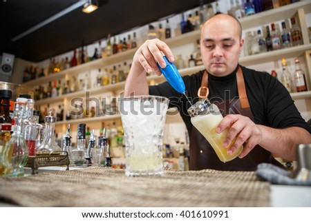 barman using a hand mixer to prepare drink in  bar or pub - stock photo