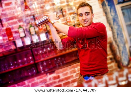 barman using a shake mixer cocktails and drinks in nightclub, bar or pub - stock photo
