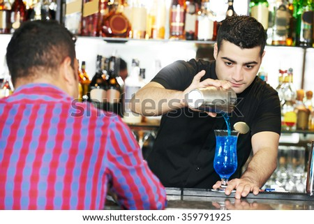 Barman worker serving cocktail in  bar - stock photo