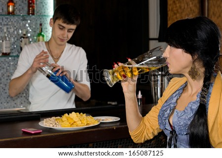Barman working behind a bar counter in a nightclub mixing cocktails watched by a young woman sipping a pint of beer - stock photo