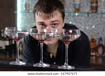 Barman working behind the bar counter peering across at the camera between three cocktail glasses lined up on the counter - stock photo