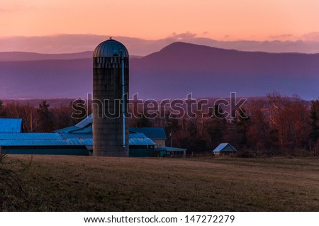 Barn and silo on a farm in the Shenandoah Valley at sunset, with Massanutten Mountain behind, near Luray, Virginia - stock photo