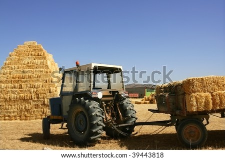 Barn stacked with pyramid shape and agriculture tractor vehicle - stock photo