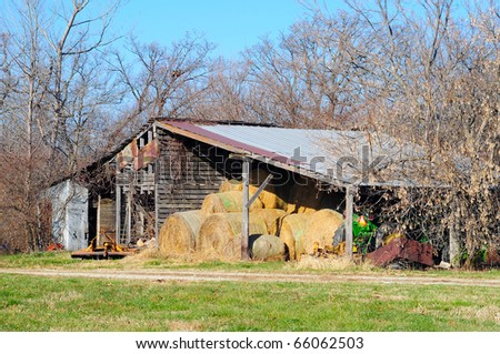 Barn with hay, straw, and tractor with copy space - stock photo