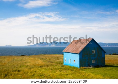 Barn with ocean in background on beautiful day. Rural scene.