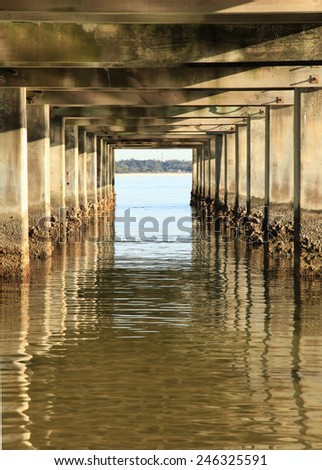 Barnacle Covered Cement Pillars of an Ocean Fishing Pier - stock photo