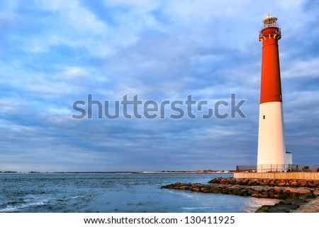 Barnegat lighthouse maritime navigation aid landmark tower in a scenic seashore seascape on the Atlantic coast of the New Jersey shore in sunset light - stock photo